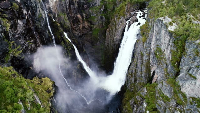 scenic aerial view of voringfossen waterfall and river - atmospheric mood stock videos & royalty-free footage