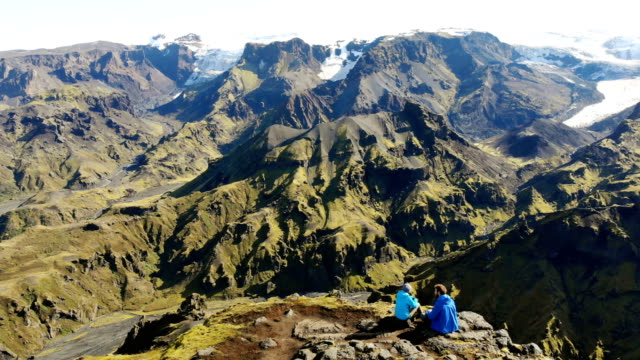 Scenic aerial view of woman and man looking at colorful mountains in Landmannalaugar in Iceland