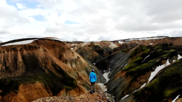 scenic aerial view of woman hiking near   colorful mountains in landmannalaugar in iceland - iceland stock videos & royalty-free footage