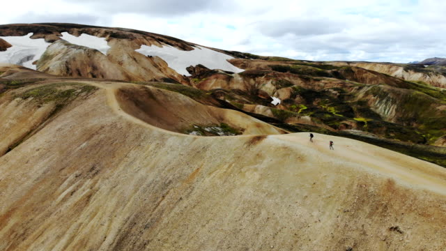 Scenic aerial view of woman hiking near   colorful mountains in Landmannalaugar in Iceland