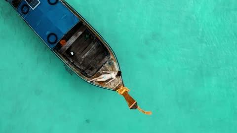 vídeos y material grabado en eventos de stock de panorámica vista aérea de la mujer tendido en el bote de cola larga en el mar - islas phi phi