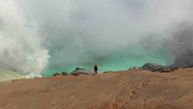 vídeos de stock e filmes b-roll de scenic aerial view of woman looking at  ijen volcano and sulphur minings - ambiente dramático