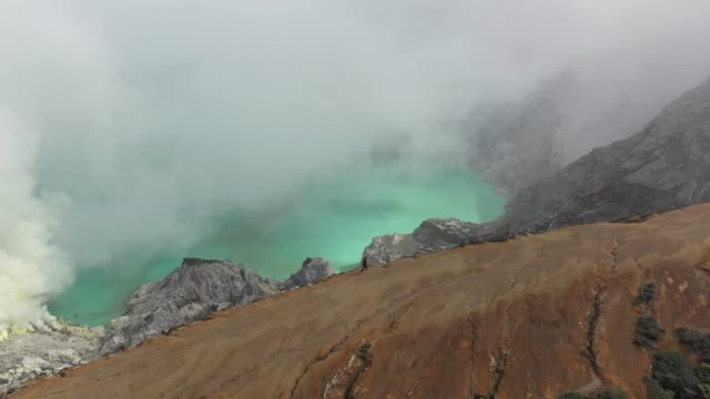 scenic aerial view of woman looking at  ijen volcano and sulphur minings - atmospheric mood stock videos & royalty-free footage