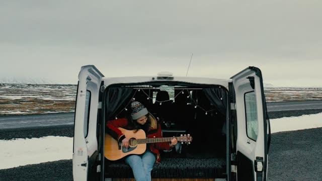 vídeos y material grabado en eventos de stock de vista panorámica aérea de mujer tocando la guitarra en autocaravana - músico