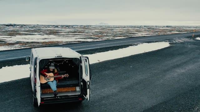 Scenic aerial view of woman  playing guitar  in camper van