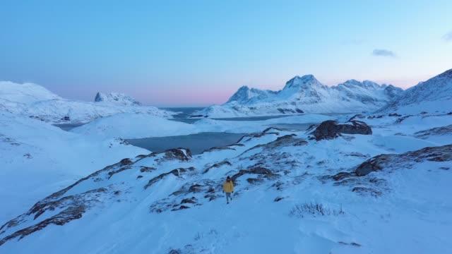 雪の中のロフォーテン島の山を歩く女性の風光明媚な空中写真 - 探求点の映像素材/bロール