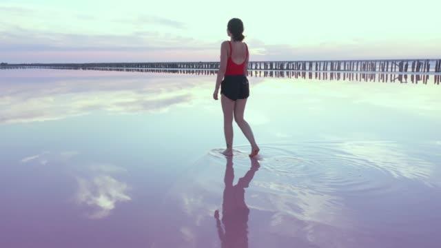 vídeos y material grabado en eventos de stock de vista aérea escénica de la mujer caminando sobre el lago salado rosa en ucrania - majestuoso