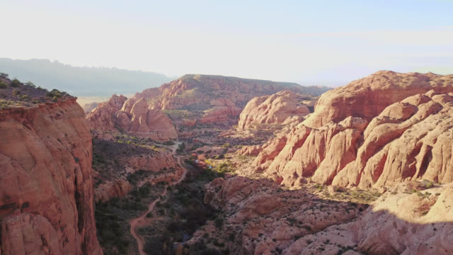 vídeos de stock, filmes e b-roll de scenic aerial view over winding river and dirt road running through majestic sandstone canyon near moab, utah. - desfiladeiro
