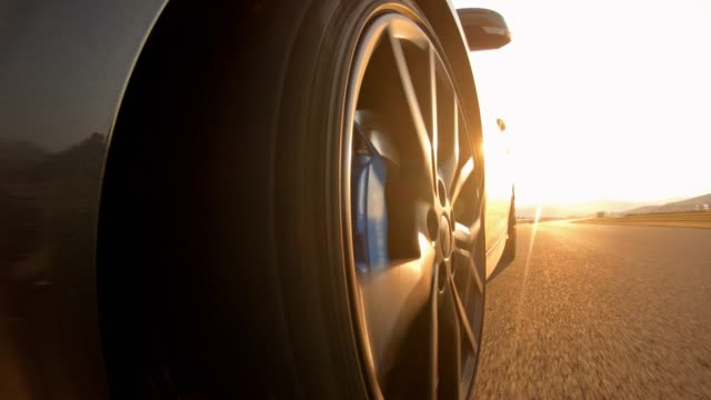 scenic car drive at sunset - wheel stock videos & royalty-free footage