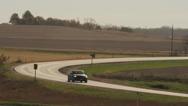 Scenic curve in a rural highway; a car passes through.