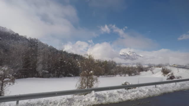 scenic driving pov view out a car window in the mountains with snow - autoperspektive stock-videos und b-roll-filmmaterial