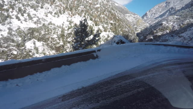 scenic driving pov view out a car window in the mountains with snow - ravine stock videos & royalty-free footage