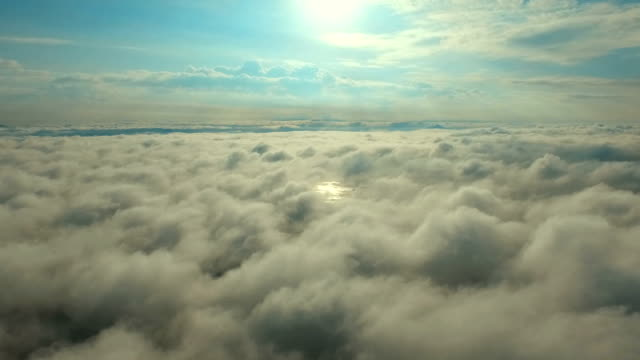 Scenic flight above the clouds towards the sun