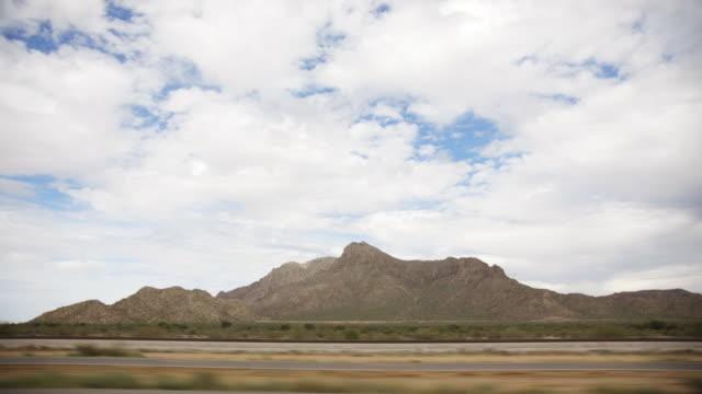 vídeos de stock, filmes e b-roll de scenic highway drive with mountain range - ponto de vista de motorista