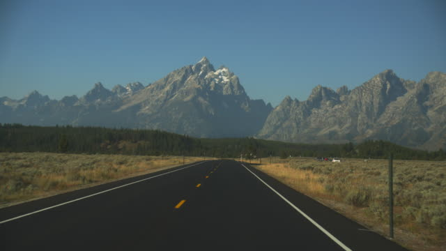 a scenic highway stretches towards grand teton national park. - grand teton national park stock videos & royalty-free footage