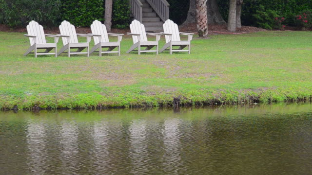 ms scenic of chairs and reflections at water stream with relaxing and peaceful feeling adronidack chairs / hilton, head south carolina, united states - fünf gegenstände stock-videos und b-roll-filmmaterial