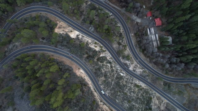 vidéos et rushes de scenic serpentine highway 89a entre sedona et flagstaff, arizona, dans le crépuscule. vidéo accélérée de drone aérien regardant vers le bas avec le mouvement panoramique de caméra. - sedona