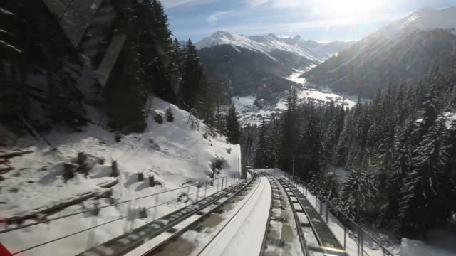 scenic shots of davos switzerland with the sun rising over snow covered mountains in the background point of view shot moves along a train track as... - ダボス点の映像素材/bロール