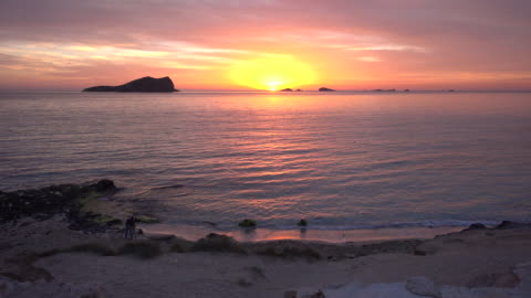 vídeos y material grabado en eventos de stock de scenic sunset over beachgoers in ibiza, wide - puesta de sol