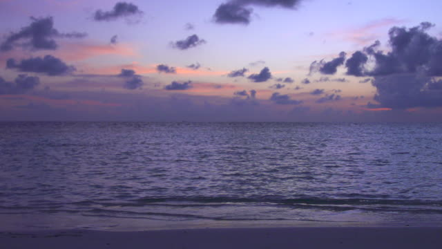 a scenic tropical beach at sunset in the maldives. - slow motion - goodsportvideo stock videos and b-roll footage