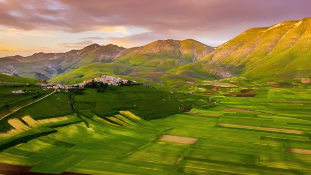 ws timelapse/hyper lapse paesaggio e città panoramici e verdi, castelluccio, umbria, italia - town video stock e b–roll