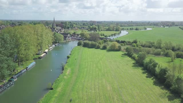 scenic view at lush green trees and grassfields with river thames in abingdon town, oxford city, uk.- aerial drone shot - barge stock videos & royalty-free footage