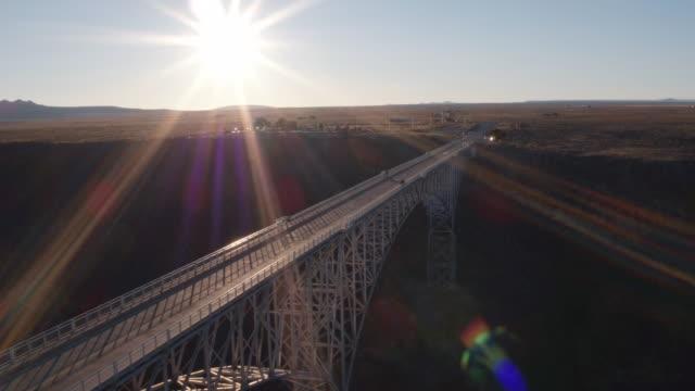 scenic view flying over bridge spanning gorge under sun - gerade stock-videos und b-roll-filmmaterial