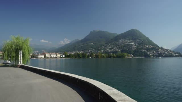 scenic view of boardwalk along lake in lugano - ticino canton stock videos and b-roll footage