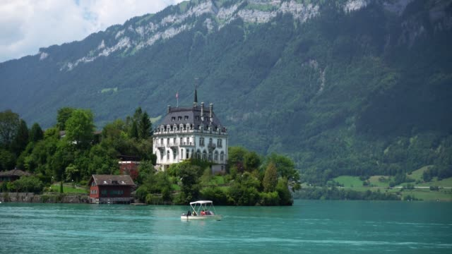 scenic view of boat on interlaken lake in switzerland - castle stock videos & royalty-free footage