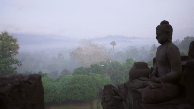 scenic view of borobudur temple at sunrise in fog - buddhism video stock e b–roll