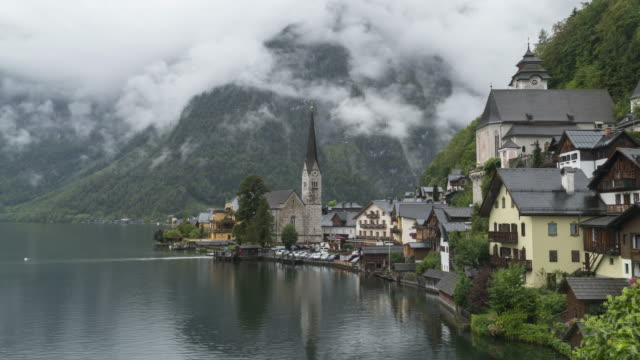 scenic view of famous hallstatt mountain village at raining day in summer - village stock videos & royalty-free footage