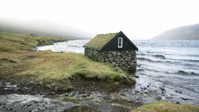 scenic view of hut with roof covered in moss near the seaside in faroe islands - atlantic islands stock videos & royalty-free footage