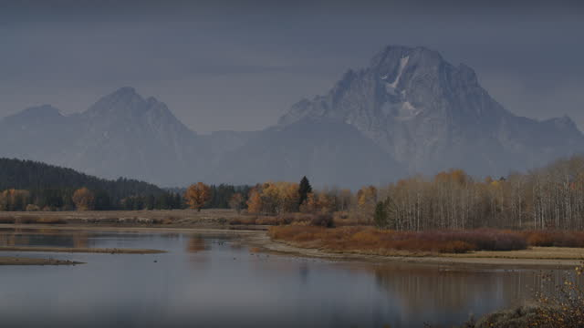 scenic view of mountain range near river bend in autumn / grand teton national park, wyoming, united states - grand teton national park stock videos & royalty-free footage