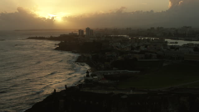 ws aerial pov scenic view of sea waves during sunrise / san juan, puerto rico, united states - sea channel stock videos and b-roll footage