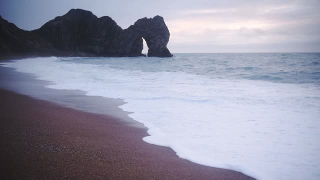 scenic view of the durdle door at lulworth cove in dorset, england with sea waves splashing on the shore - wide shot - natural arch stock videos & royalty-free footage