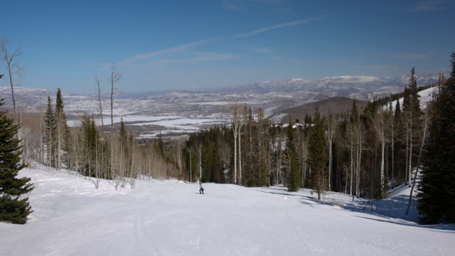 scenic view of tourists skiing over snowy mountain on sunny day - park city, utah - park city stock videos & royalty-free footage