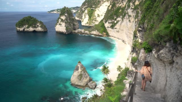 scenic view of woman looking at beach from the cliff on  nusa penida - bali stock videos & royalty-free footage