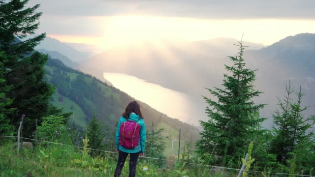 scenic view of woman looking at  lake in swiss alps at sunset - raincoat stock videos & royalty-free footage