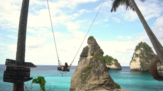 scenic view of woman on swing above the sea on nusa penida - bali stock videos & royalty-free footage