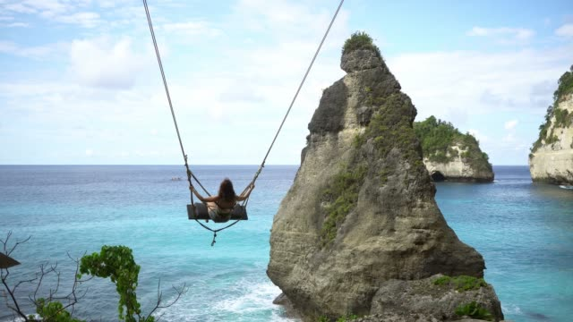 scenic view of woman on swing above the sea on nusa penida - reportage stock videos & royalty-free footage