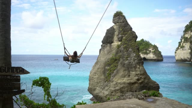 scenic view of woman on swing above the sea on nusa penida - rope swing stock videos & royalty-free footage