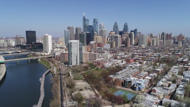 vidéos et rushes de vue panoramique sur le centre-ville de philadelphie au-dessus de schuylkill river park au début du printemps.  mouvement panoramique de la caméra - philadelphie