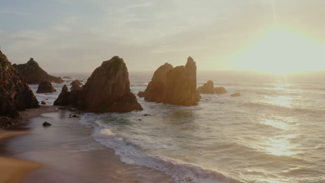 vídeos de stock e filmes b-roll de aerial ws scenic views praia da ursa beach in portugal - dusk