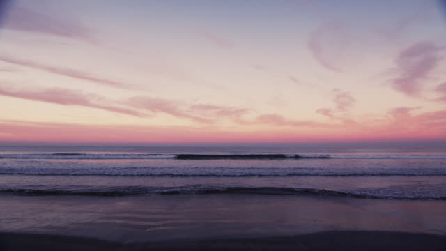 Scenic wide-angle surf shot of wave breaking on a colorful horizon at sunset.Original stock color video shot in 6K by a RED Dragon camera.