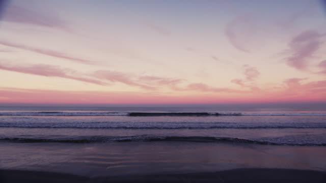Malerische Weitwinkel Surf Schuss Welle brechen auf einen bunten Horizont bei Sonnenuntergang. Original auf lagerfarbe Video gedreht in 6K durch eine RED Dragon-Kamera.