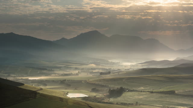 T/L scenics of mist rolling over Hemel en Aarde Valley as clouds move across sky, Hermanus, South Africa