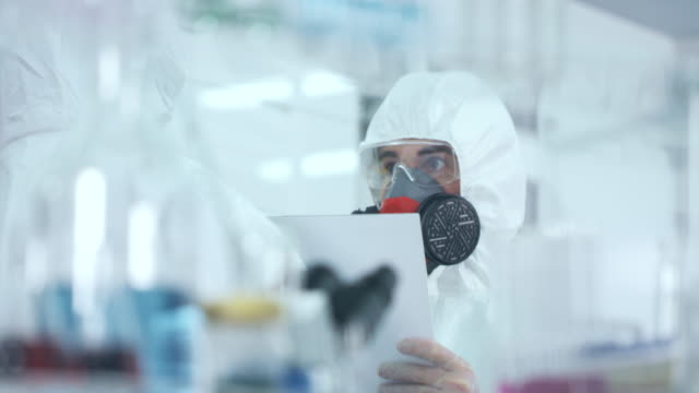 vídeos de stock e filmes b-roll de scentist in lab wearing protective suits is worried - preocupado