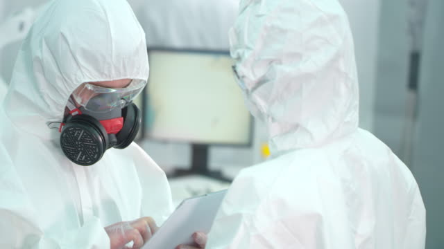 scentists in lab wearing protective suits are talking - epidemiology stock videos & royalty-free footage