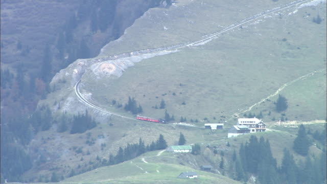 schafberg mountain railway train departs from station as it begins mountain ascent, st wolfgang, austria - オーストリア点の映像素材/bロール