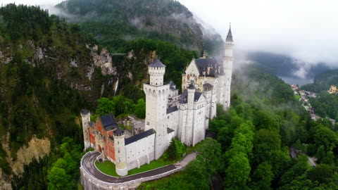 schloss neuschwanstein castle stands in this aerial view in the early morning on june 11, 2015 near hohenschwangau, germany. schloss neuschwanstein,... - castle stock videos & royalty-free footage